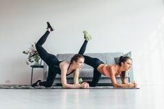 2 подходящих женщины делая согнутого осла колена пинают тренировку в всем положении fours разрабатывая их батокс дома стоковая фотография