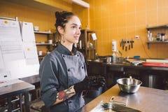 Подчиненное печенье профессии и варить молодая кавказская женщина с татуировкой кондитера в кухне ресторана подготавливая круг стоковое изображение
