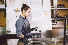 Подчиненное печенье профессии и варить молодая кавказская женщина с татуировкой кондитера в кухне ресторана подготавливая круг стоковое фото