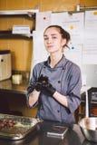 Подчиненное печенье профессии и варить молодая кавказская женщина с татуировкой кондитера в кухне ресторана подготавливая круг стоковые изображения