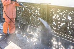 Подъездная дорога работника очищая с шайбой давления бензина высокой брызгая грязь, перила, мост бамперов Высокая чистка давления стоковое фото rf