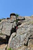 Подъемы альпиниста утеса девушки на утесе Стоковая Фотография RF