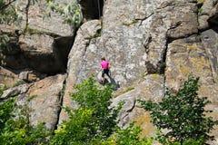 Подъемы альпиниста утеса девушки на утесе Стоковая Фотография