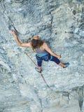 Подъемы альпиниста утеса женщины на скале Стоковые Фотографии RF