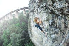 Подъемы альпиниста утеса женщины на скале Стоковое Изображение