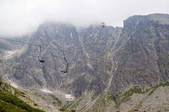 Подъем кабины к горе Ландшафт горы в высоком Tatry Подвесной подъемник на лыжном курорте в облаке Подъем лыжи, кабина фуникулера  стоковое фото