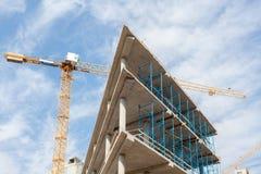 подъем конструкции здания высокий вниз Место с кранами против голубого неба Стоковые Изображения RF