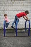 Подъем мальчика и девушки на автостоянке велосипеда Стоковые Фотографии RF