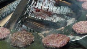 Подъем руки жаря мясо бургера на гриле утюга Handheld съемка замедленного движения сток-видео