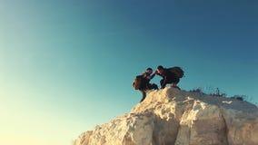 Подъем товарища по команде порции альпиниста, человек с рюкзаком достиг вне руку помощи к его другу Друг порции Hiker акции видеоматериалы