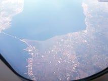 Под крылом самолета Панорамный взгляд голубого неба с облаками и ` s земли отделывают поверхность от высоты Стоковая Фотография RF