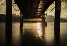 Под мостом на заходе солнца стоковое фото rf