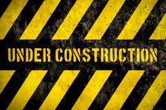Под предупредительным знаком конструкции при желтые и темные нашивки покрашенные над фасадом бетонной стены грубым как предпосылк Стоковые Фото