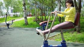 Поезда молодой женщины на неподвижных имитаторах на открытом воздухе видеоматериал