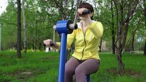 Поезда молодой женщины на неподвижных имитаторах на открытом воздухе акции видеоматериалы