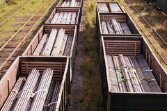 2 поезда на автомобилях железной дороги которые стальные заготовки для труб стоковое изображение