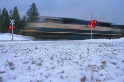 Поезд быстро проходит через пересечение дорог в зиме Стоковая Фотография