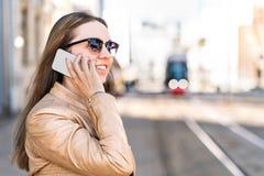 Поезд города молодой женщины ждать и говорить на телефоне стоковые фотографии rf