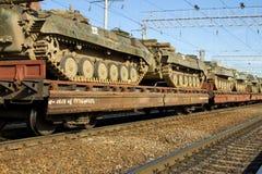 Поезд груза нося воинские танки на железнодорожных плоских фурах Стоковое Изображение