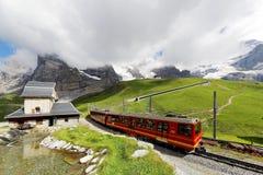 Поезд колеса Cog путешествуя на железной дороге Jungfrau от верхней части станции Jungfraujoch Европы к Kleine Scheidegg Стоковые Изображения RF