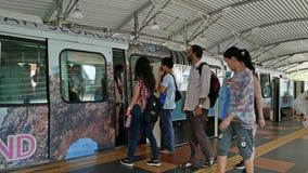 Поезд монорельса KL приезжая к станции и толпе людей получая в и из поезда видеоматериал