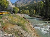 Поезд пара вдоль потока горы стоковое фото