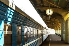 Поезд стоит на платформе станции Часы станции стоковые изображения