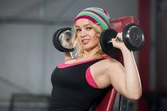 Поезда женщины в спортзале с гантелями Стоковая Фотография