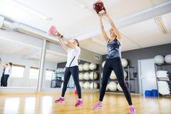 2 поезда женщин с kettlebells на спортзале фитнеса стоковые фотографии rf