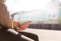 Поезд женщины ждать в платформе и smartphone использования для того чтобы купить e-билет или план-график просматривать стоковое фото