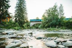 Поезд идет через реку горы старым мостом Стоковое Фото