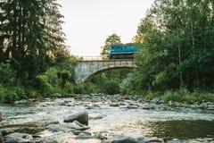 Поезд идет через реку горы старым мостом Стоковые Фото