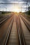 Поезд прокладывает рельсы движение запачканное заходом солнца стоковые фото