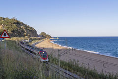Поезд проходя пляжем Calella Стоковая Фотография RF