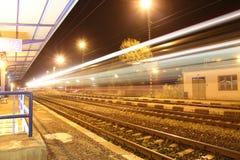 Поезд проходя станцию на ночу Стоковые Изображения