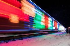 Поезд украшенный с светами праздника приезжает на станцию Стоковые Изображения RF
