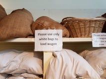 Пожалуйста используйте только белые сумки для того чтобы нагрузить знак фуры на полке стоковые фотографии rf