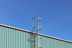 Пожарная лестница металла на крыше промышленного здания против голубого неба Безопасность работы людей Опорожнение во время stoi стоковая фотография
