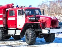 Пожарная машина на столбе около древесины в зиме Стоковая Фотография