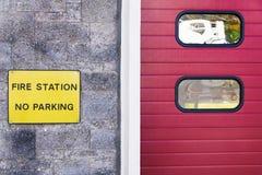 Пожарное депо отсутствие знака стоянки на стене и красной двери шторки стоковые изображения rf