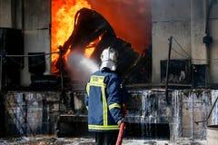 Пожарные борются для того чтобы потушить огонь который сломал вне на a стоковые изображения