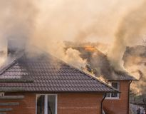 Пожарные воюя бушующий пожар с огромными пламенами горящего timbe стоковое изображение rf