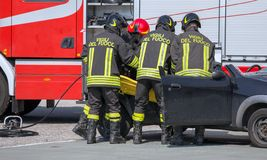 Пожарные вытягивают внутри раненный автомобилем Стоковое фото RF