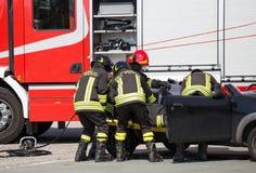 Пожарные вытягивают внутри раненный плитами автомобиля после того как авария дороги Стоковые Фото