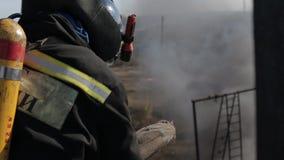 Пожарные в маске противогаза во время огня, снимая видеоматериал