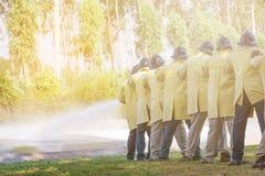 Пожарные используя гаситель и воду от шланга для пожаротушения стоковые изображения rf