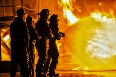 Пожарные ЙОХАННЕСБУРГА, ЮЖНОЙ АФРИКИ - мая 2018 распыляя вниз с огня во время учебного упражнени firefighting стоковые изображения