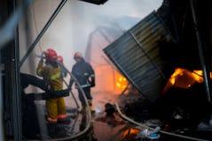 Пожарные на огне Пожарный тушит огонь с водой Внешний рынок на огне Из фокуса стоковая фотография