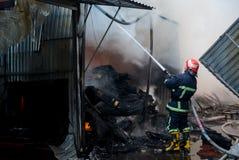 Пожарные на огне Пожарный тушит огонь с водой Внешний рынок на огне Стоковое фото RF