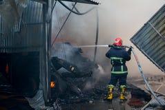 Пожарные на огне Пожарный тушит огонь с водой Внешний рынок на огне Стоковое Фото